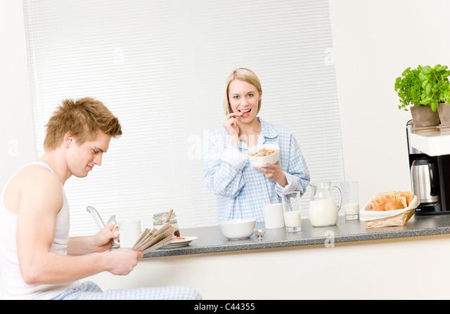 Breakfast happy couple eat cereal drink coffee in kitchen - Stock-Bilder