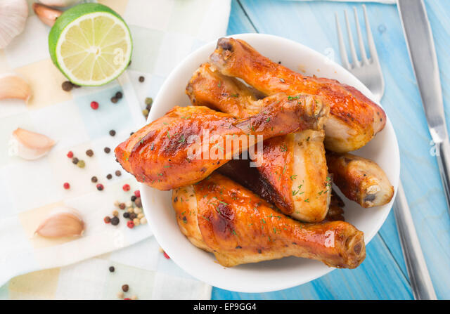 Delicious roasted chicken legs in a bowl - Stock Image