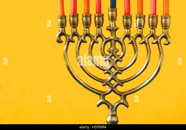 Hanukkah menorah with candles on the yellow background horizontal - Stock Image