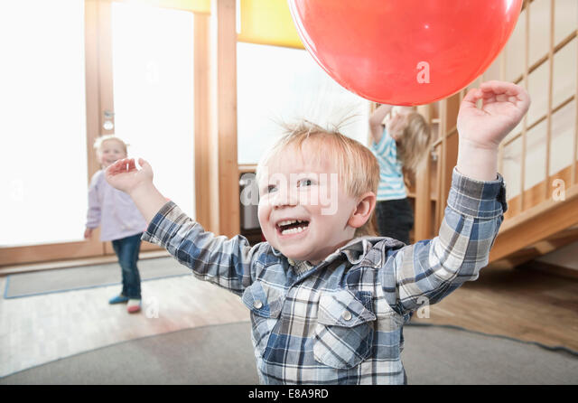 Kids playing with red balloons in kindergarten - Stock Image