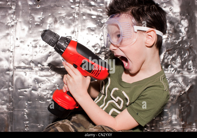 Boy with power tool and safety goggles - Stock Image