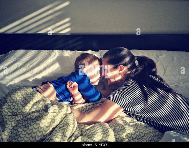 Mother and son in bed in sunlight - Stock Image