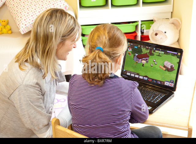 teacher helping young girl to use a computer, playing a computer game - Stock Image