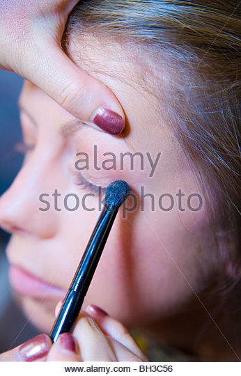 Close-up of woman getting eyeshadow applied - Stock Image