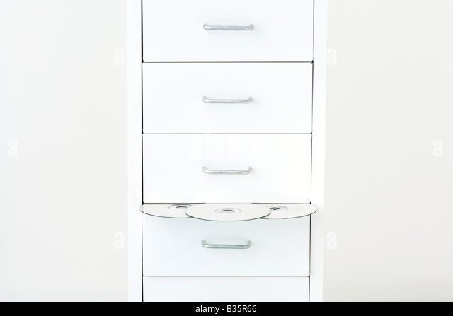 DVDs emerging from filing cabinet - Stock Image