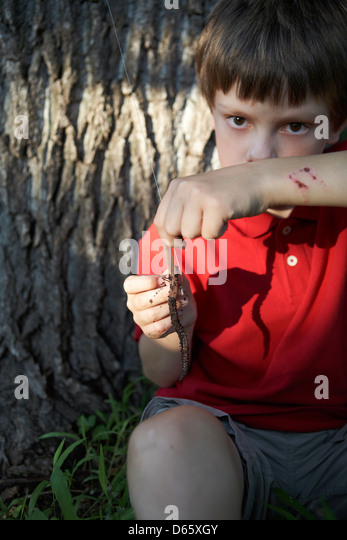 8 year old boy hooking earth worm - Stock Image