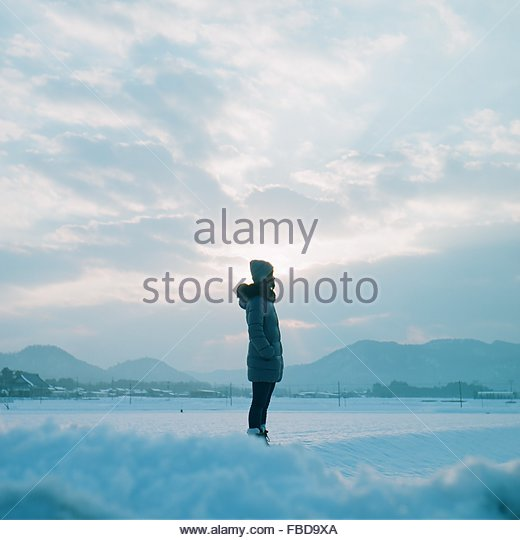 Woman Standing On Snow Covered Field Against Sky - Stock Image