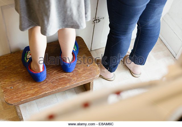 Legs of mid adult mother next to daughter standing on stool in kitchen - Stock Image