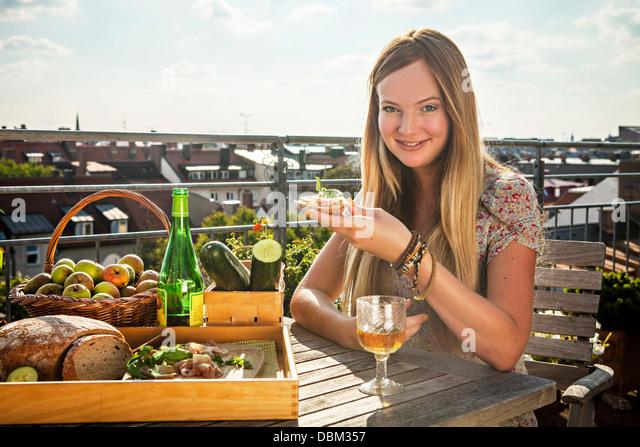 Young Woman Eating On Balcony, Munich, Bavaria, Germany, Europe - Stock-Bilder