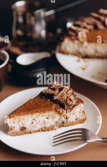 Slice of cheesecake on plate with fork - Stock Image
