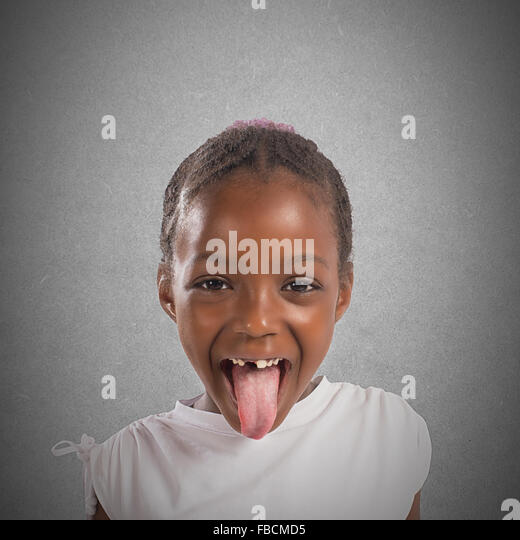 Little girl makes a tongue - Stock Image