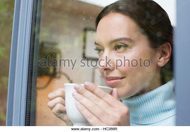 Mid adult woman drinking coffee at window. - Stock-Bilder