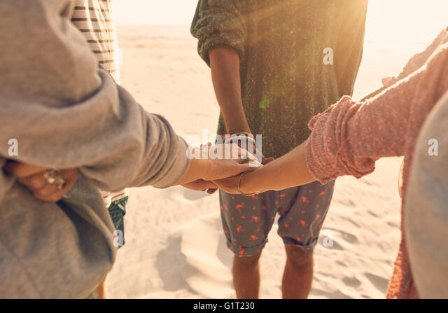Group of friends stack their hands together. Young men and women standing together at the beach stacking their hands, - Stock Image