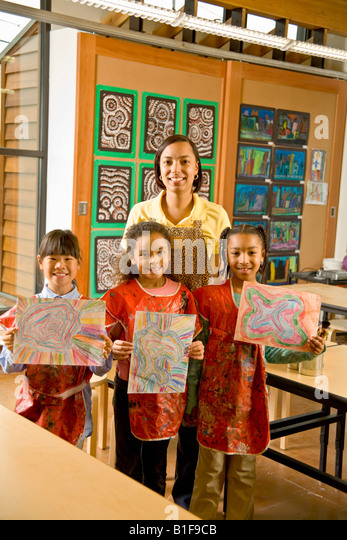 African art teacher and students holding paintings - Stock-Bilder