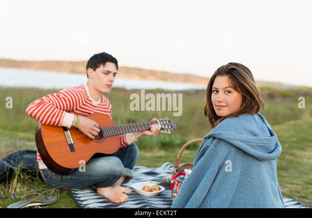 Rear view portrait of teenage girl with boyfriend playing guitar during picnic - Stock Image