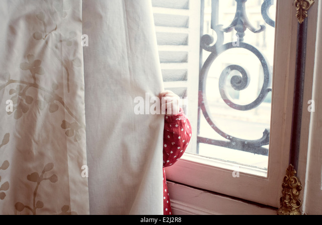 Child hiding behind curtain - Stock-Bilder