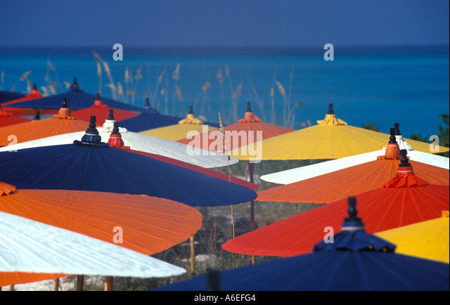 Beach umbrellas red yellow blue white orange blue water background bright colors - Stock Image