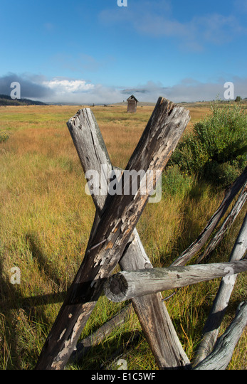Broken fencing on grassland, and a barn in the open in the Green River lakes area. - Stock Image