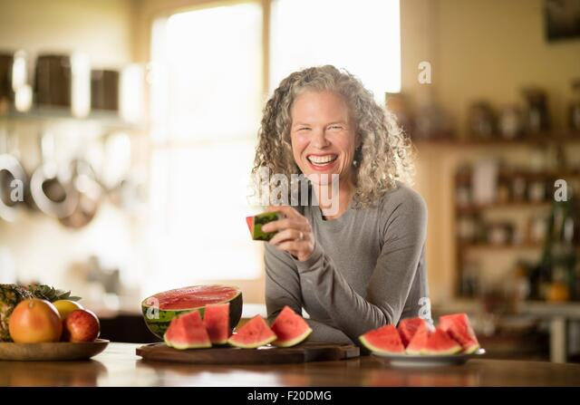 Portrait of mature woman eating watermelon in kitchen - Stock Image