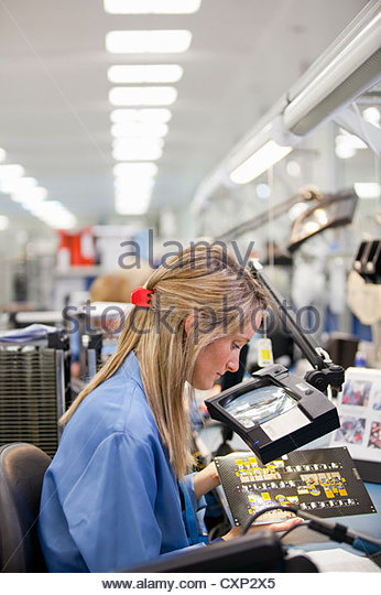 Technician examining printed circuit board in hi-tech electronics manufacturing plant - Stock Image