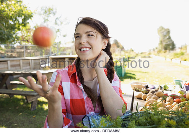 Playful woman tossing apple in community garden - Stock Image