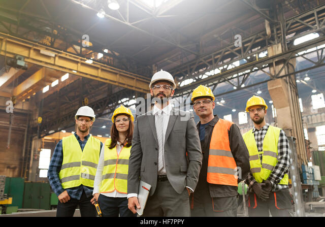 Portrait confident manager and steel worker team in factory - Stock Image
