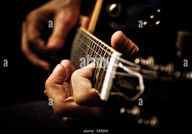 Canada, Quebec, Montreal, Close up of young man playing acoustic guitar - Stock Image