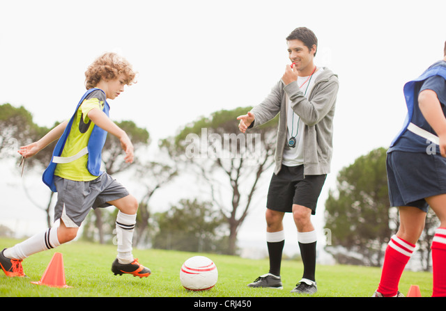 Coach training childrens soccer team - Stock Image