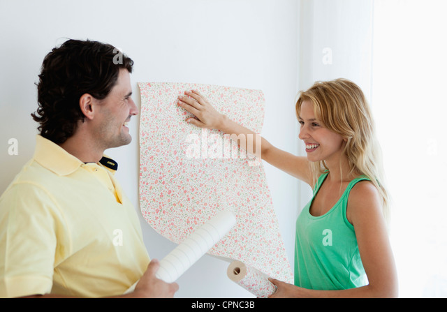 Couple decorating new house with wallpaper - Stock Image