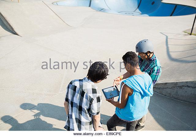 Teenage boys with digital tablet at skateboard park - Stock Image