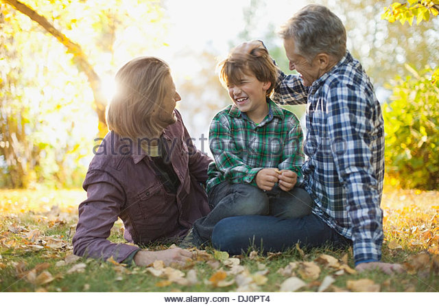 Cheerful three generation males spending leisure time at park - Stock Image