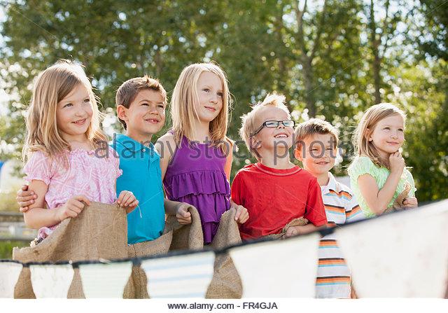 Young cousins waiting to start potato sack race. - Stock Image