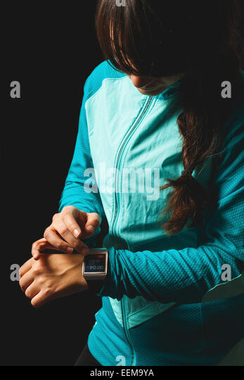 Young woman looking at smart watch - Stock Image
