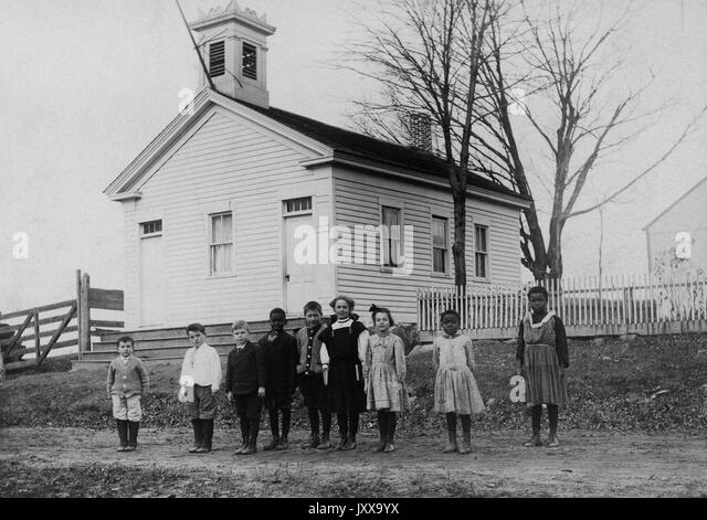 Full length landscape shot of nine students standing outside schoolhouse, three African American students, 1920. - Stock Image