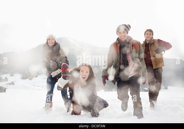 Portrait of friends playing in snowy field - Stock-Bilder