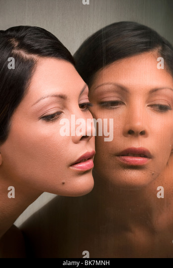 Young Hispanic woman and her mirror reflection - Stock Image