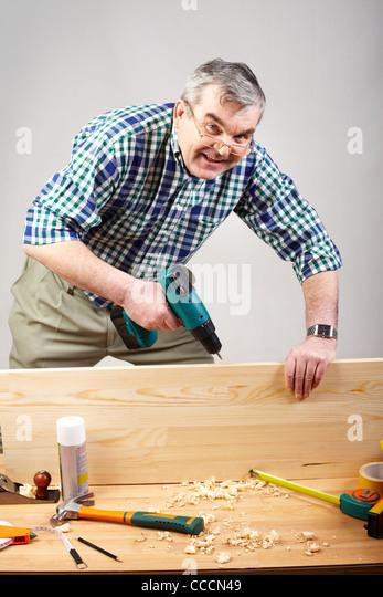 Senior man drilling plank in workshop - Stock-Bilder