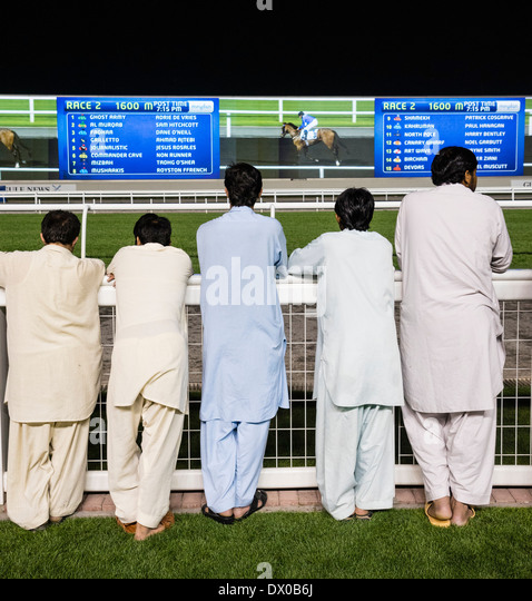 Spectators at horse racing meeting at Al Meydan racecourse at night in Dubai United Arab Emirates - Stock Image