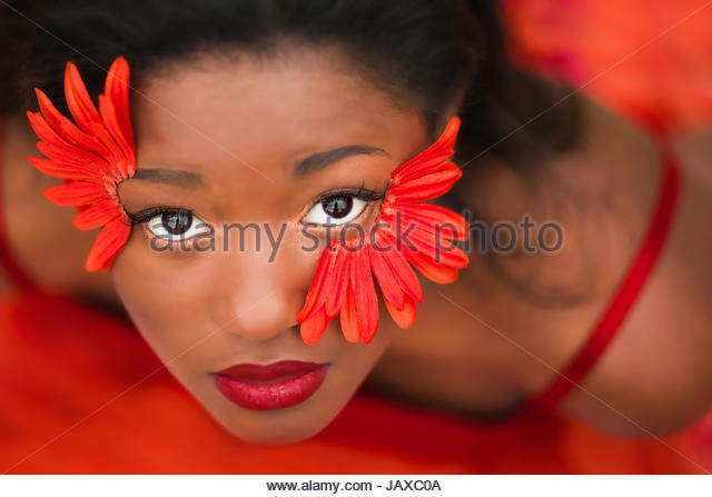 Young woman looking up with red  flower petals on her face - Stock Image