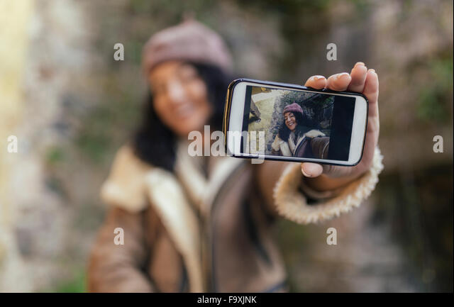 Selfie of smiling woman on display of smartphone - Stock Image