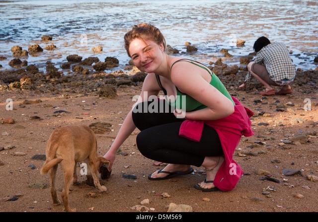 Madagascar, Nosy Be, Marodokana, Operation Wallacea student petting dog on beach - Stock Image