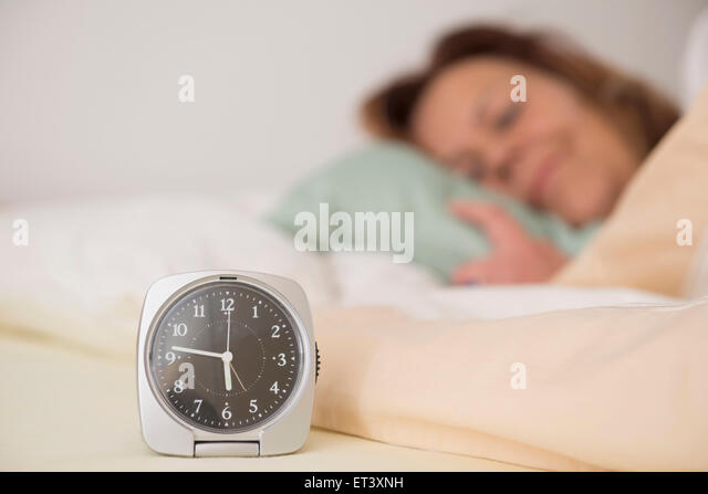 Woman asleep in bed while her alarm shows the early time at home in bedroom, Munich, Bavaria, Germany - Stock Image