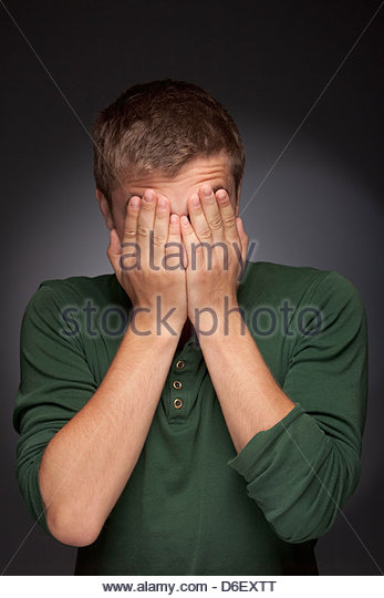 Teenager boy man portrait shy hands covering face - Stock Image