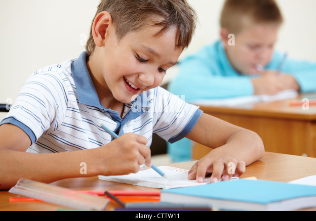 Portrait of smart lad drawing at lesson with classmate on background - Stock Image