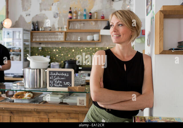 Mid adult woman in cafe - Stock Image