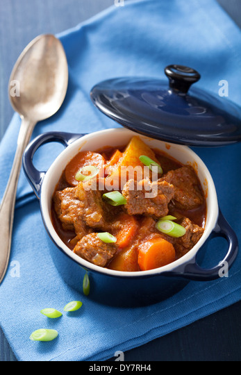 beef stew with potato and carrot in blue pot - Stock Image