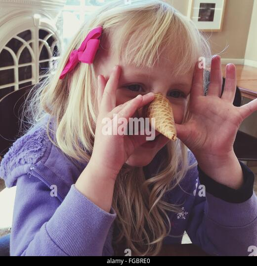 Cute Girl Playing With Ice Cream Cone At Home - Stock Image