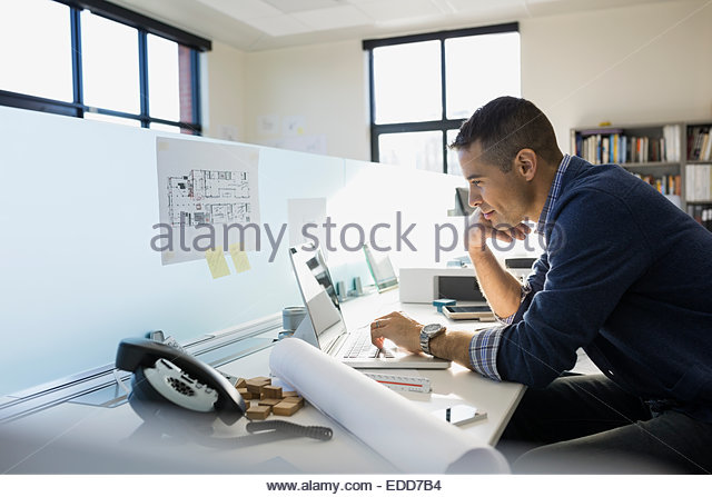 Architect working at laptop in office - Stock Image