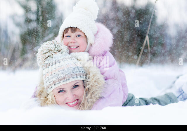 Happy parent and kid playing with snow in winter outdoor - Stock Image