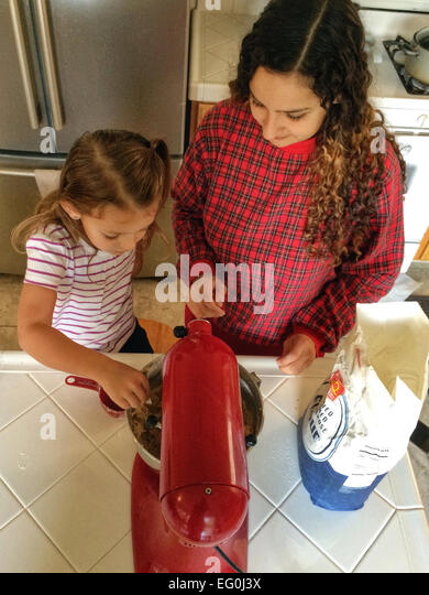Girl (4-5) cooking with her mom - Stock Image